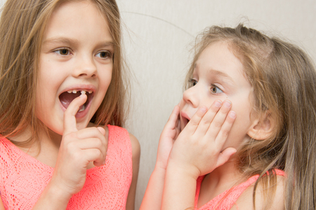 Six year old girl shows her sister a four wobbly front tooth milk