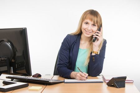 assigned: Business woman talking on the phone, writing in a notebook, and looked into the frame Stock Photo