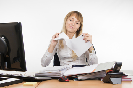 Business girl having fun tearing the paper document