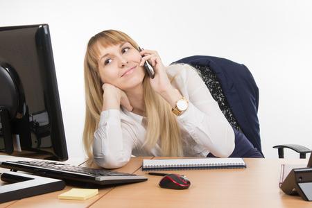 Happy business woman having fun talking on a cell phone in the office Foto de archivo