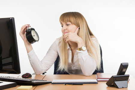 sadly: Office employee sadly looks at the clock with time nine oclock five minutes in the morning