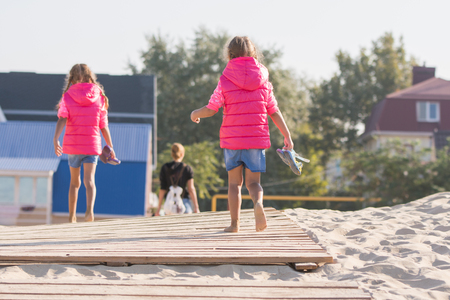 come home: Mother and two daughters go to dawn on the wooden flooring in the sand, one girl turned