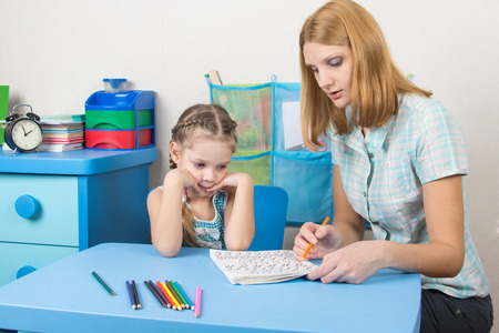 teaching material: Five-year girl with interest looks at the teaching material explained by an adult Stock Photo