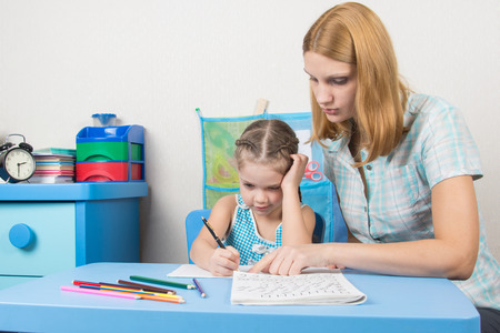 out of engagement: Tutor teaches the child to write letters Stock Photo