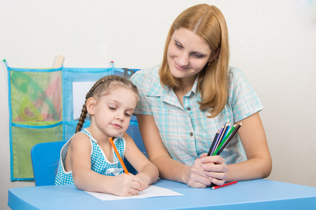 turns of the year: The five-year child draws on a sheet of paper, next to the teacher holds pencils