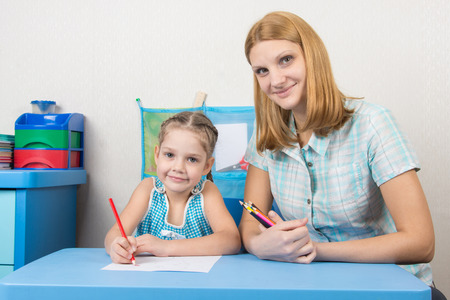 five year old: Mentor and five year old child draw with pencils sitting at the table Stock Photo