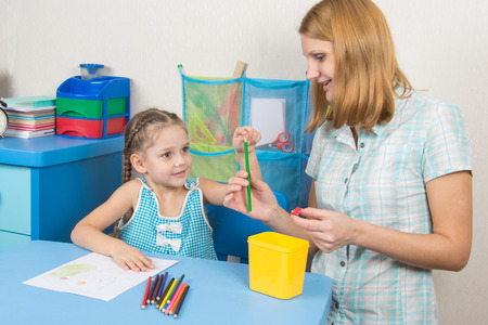 turns of the year: The five-year child put a finger on the tip of a pencil mom