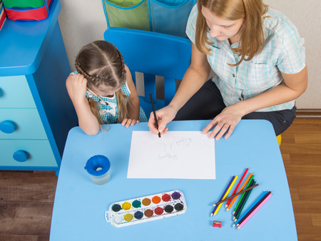 five year old: Mentor and five year old girl at the table draw a picture in kindergarten