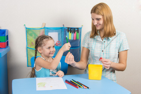 turns of the year: Five-year girl takes pencil from mother hands Stock Photo