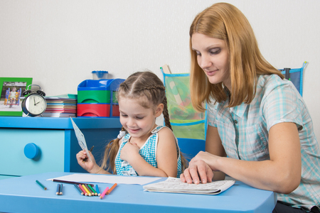 turns of the year: Girl enjoys painting with teacher in kindergarten
