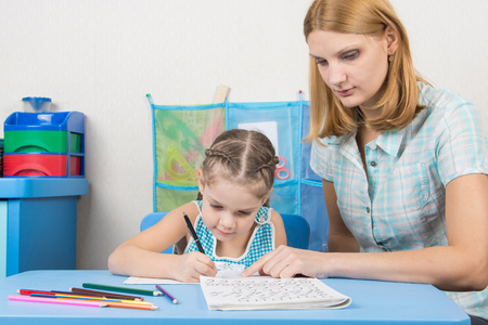 out of engagement: Tutor helps the child to spell the alphabet