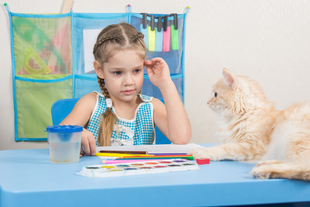 looked: Five-year girl drawing pencils looked at the cat