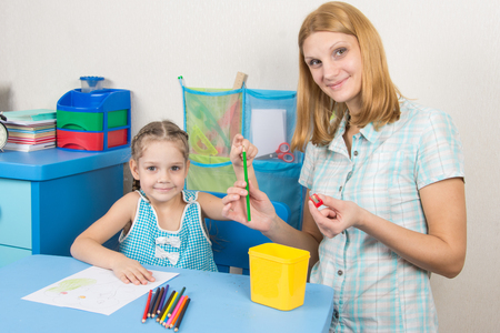 finger tip: The five-year child put a finger on the tip of a pencil mother, and together looked in the frame