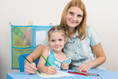 maestra enseñando: niña de cinco años y la joven madre juntos pintan un cuadro en una hoja de papel