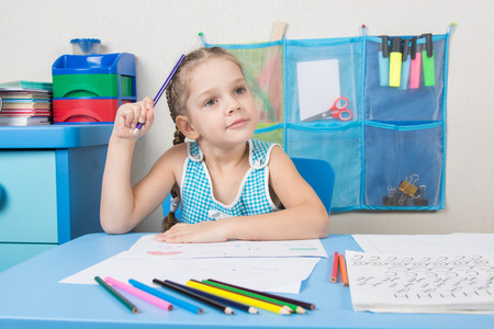 wondered: Five-year girl scratched his head and wondered pencil drawing picture at table Stock Photo