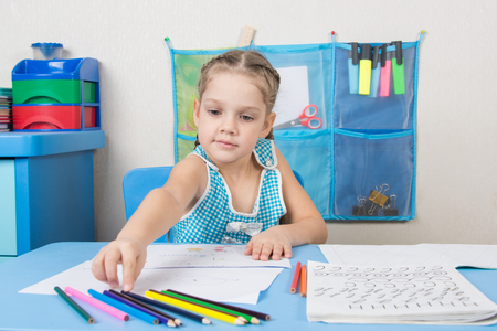 Five-year girl choose the right pencil doing painting Stock Photo