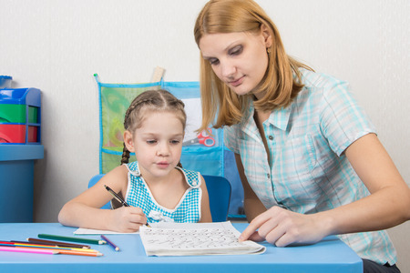Female foster parent helping mentor her foster child by helping with homework.