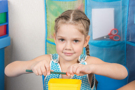 five year old: Happy five year old girl sharpens a pencil sharpener small