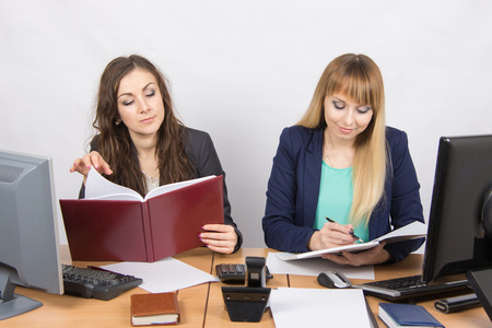 careerist: Two business women working in the office with one desk