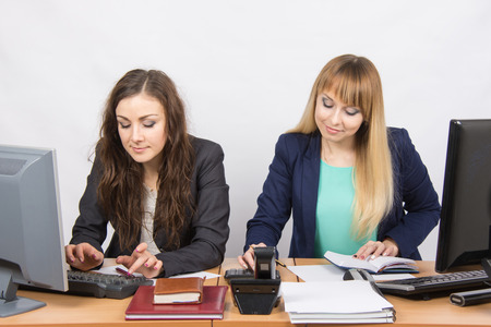careerist: Two young business women working in the office at the workplace at the same table