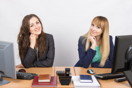 Two young girls newly recruited developing are in the workplace Standard-Bild