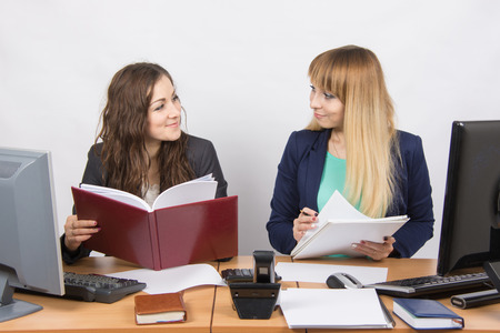 mutually: Two business rivals girls look at each other while sitting at a desk