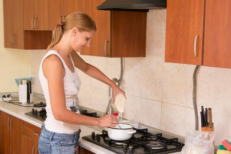 casalinga: Ragazza casalinga prepara il porridge in cucina