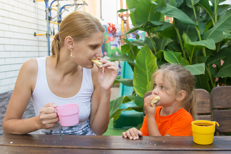 five year: pretty young mother and five year old daughter having breakfast on the veranda