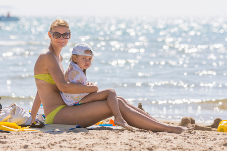 five year old: Young mother sitting with frozen five year old daughter on the beach and cherishes it