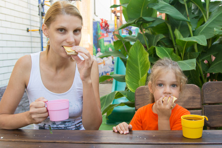 five year old: pretty young mother and five year old daughter having breakfast on the veranda