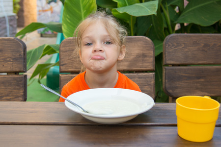 insipid: Five-year girl sits at a table with a sour face and did not want to eat porridge for breakfast
