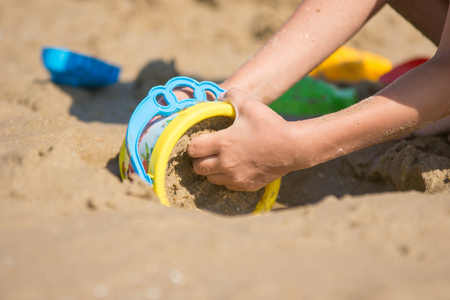 gaining: The baby is gaining a bucket in the wet sand, close-up, on the sandy beach of the seaside