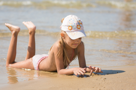lies: Six-year girl lies on the sand of the sea, and drawing with your fingers in the sand