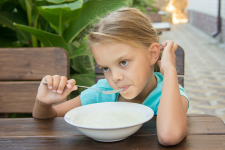 insipid: Six-year girl sitting at a table with a sour face and did not want to eat porridge for breakfast Stock Photo