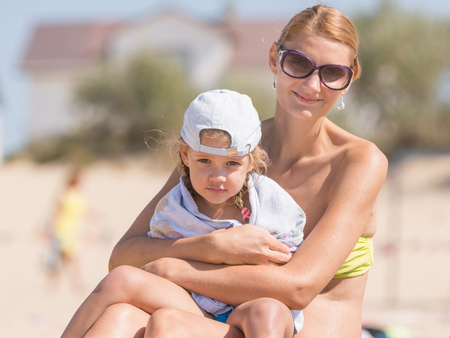 five year old: Young mother sitting with frozen five year old daughter on the beach and cherishes it wrapped in a towel Stock Photo