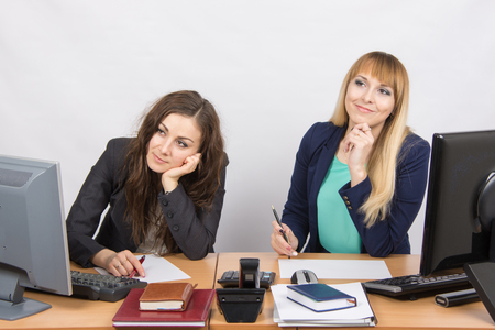 careerist: The situation in the office - two women dreaming, sitting at a desk