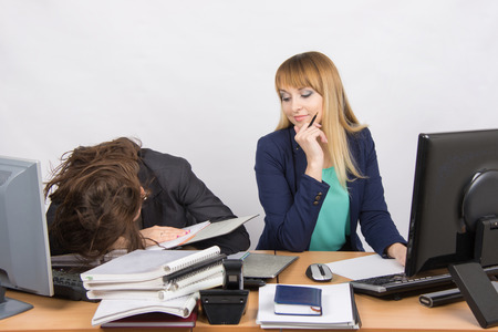 sneer: Female colleagues in the office, one had fallen asleep on a pile of folders, the second with a sneer looks at her Stock Photo