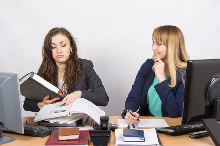 inundated: The situation in the office - one employee overburdened, the other does nothing and laughs looking at her
