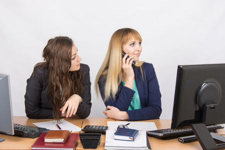 slacker: The situation in the office - the employee waits for her colleague, talk on the phone Stock Photo