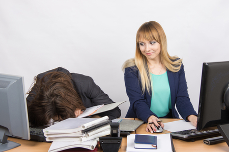 slacker: Female colleagues in the office, one had fallen asleep on a pile of folders, and the second looked at her