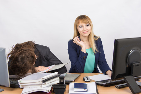 slacker: Female colleagues in the office, one had fallen asleep on a pile of folders, the other happily looking at the monitor screen Stock Photo