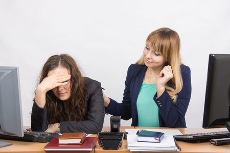 dismissed: The girl in the office soothes the dismissed colleague