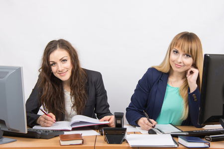 looked: Two business women writing in paper documents sitting at a desk and looked in the frame