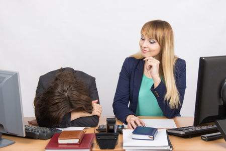 careerist: The situation in office - frustrated woman lay on the table, her colleague looking at her haughtily