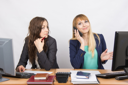 slacker: The situation in the office - a girl with a puzzled look on his colleague is talking on the phone