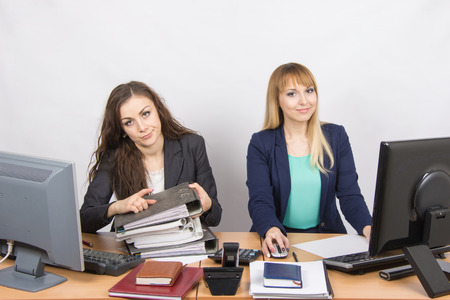 one sheet: Female colleagues in the office, one littered with paper documents, the second sitting with a blank sheet of paper Stock Photo