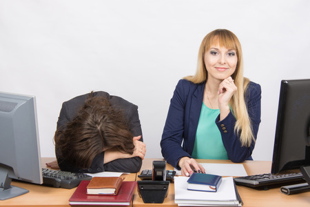 careerist: The situation in office - frustrated woman lay on the table, her colleague happily looks into the frame Stock Photo