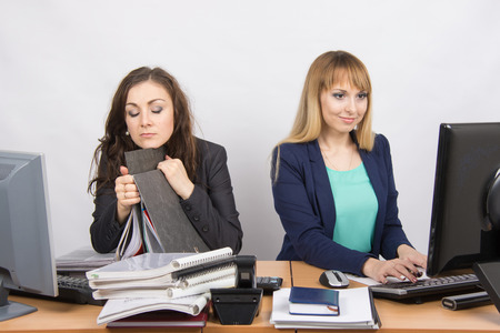 slacker: Female colleagues in the office, one asleep on a folder, the other happy working on a computer Stock Photo