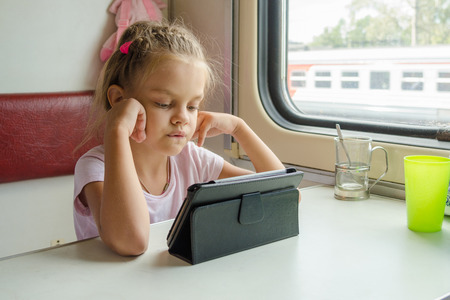 economy class: Six-year girl sitting on a train looking cartoon Tablet PC Stock Photo