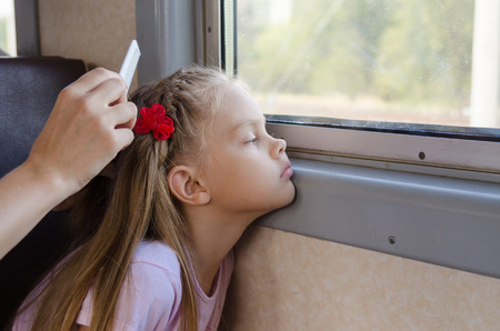 six year old: sad six year old girl looking in the window while sitting in an electric train until my mother combs her long hair